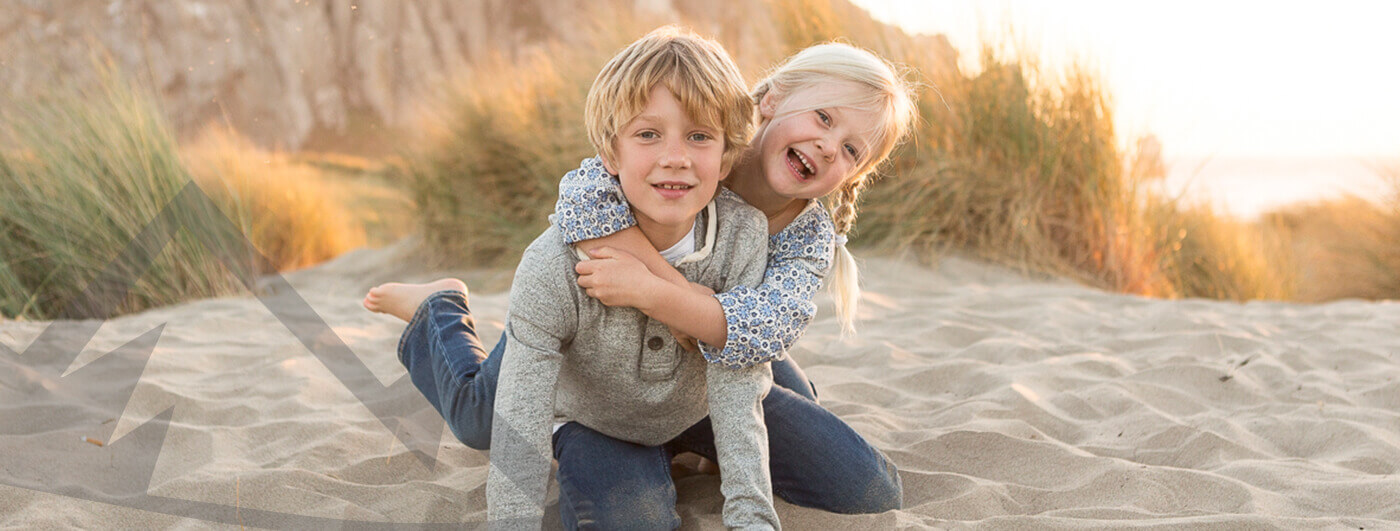 Two laughing kids on beach