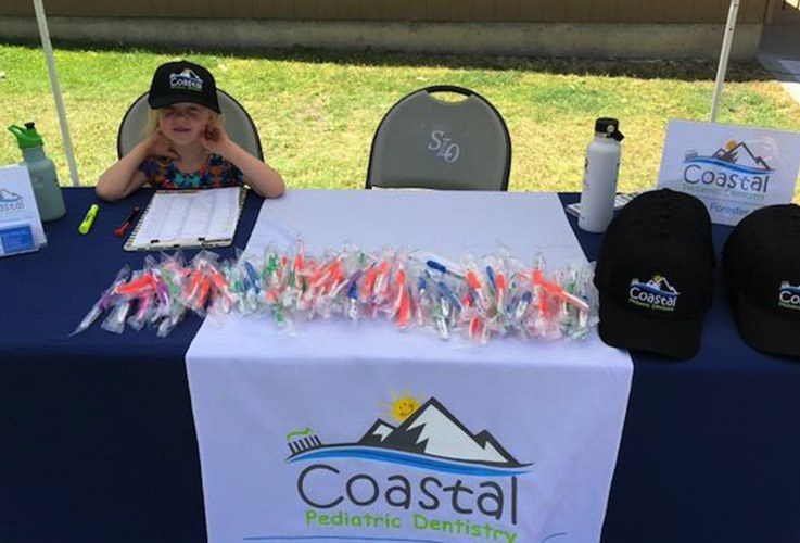 Child at Coastal Pediatric Dentistry information table