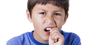 Preteen boy grimacing and holding tooth