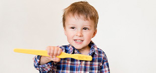 Little boy holding large toothbrush