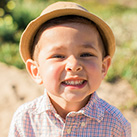Smiling little boy with hat outdoors