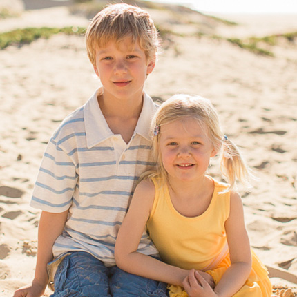Brother and sister smiling on the beach