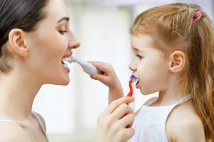 Mom and daughter brushing their teeth.
