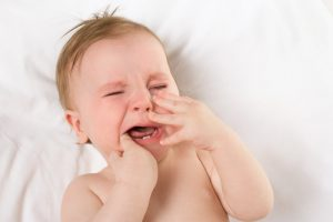 Crying baby experiencing tooth pain.